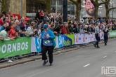 De laatste loper van de NN Marathon Rotterdam op de Coolsingel in Rotterdam
