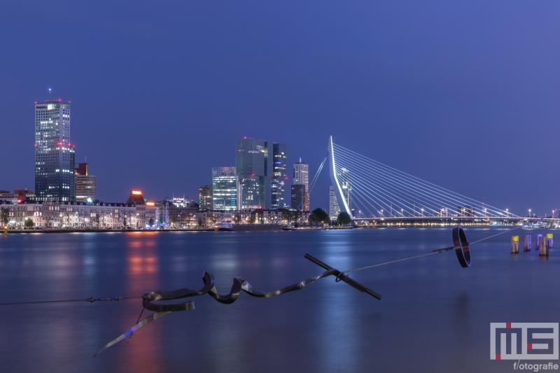 Te Koop | Het Maasbeeld (Wasknijper) in de avond met het Noordereiland, Erasmusbrug en De Maas