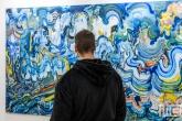 Een kleurig schilderij met bezoeker tijdens Art Rotterdam in de Van Nelle Fabriek in Rotterdam