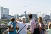 De bezoekers van de Rotterdamse Dakendagen op het Groothandelsgebouw in Rotterdam met uitzicht op de Euromast