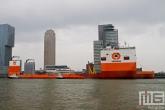 Het half-afzinkbaar transportschip Dockwise Vanguard met sleepboot Thamesbank aan de Wilhelminapier in Rotterdam
