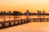 Te Koop | Het uitzicht op de skyline van Rotterdam vanaf de Kralingseplas tijdens zonsondergang