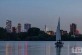 Het uitzicht op de skyline van Rotterdam met een zeilboot op de Kralingseplas