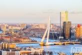 De gouden zonsondergang in Rotterdam met de Erasmusbrug en Maastoren