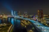 De skyline van Rotterdam by Night met de Erasmusbrug en Wilhelminapier