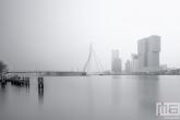Een mistige skyline van Rotterdam vanuit de Veerhaven in zwart/wit